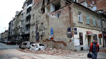 Seorang pria berjalan melewati sebuah bangunan yang rusak dan mobil-mobil hancur oleh puing-puing setelah gempa di jalan-jalan pusat kota Zagreb (22/3/2020).  Gempa magnitudo 5,3 ini tercatat sebagai yang terbesar, yang mempengaruhi Kroasia dalam 140 tahun. (AFP/Damir Sencar)