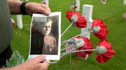 Mark Shively menunjukkan foto kakeknya dari Korps Marinir AS saat upacara Hari Peringatan Perang Dunia I di Pemakaman Amerika Aisne-Marne di Belleau, Prancis (27/5). (AP Photo / Virginia Mayo)