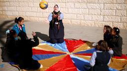 Hiba Al-Sharfa bermain bola bersama muridnya di sekolah Asosiasi Hak Hidup di Kota Gaza (21/12). Hiba Al-Sharfa telah membuktikan bahwa Down Syndrome tidaklah menjadi hambatan untuk meraih cita-citanya. (Reuters/Suhaib Salem)