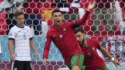Jerman kebobolan terlebih dahulu pada menit ke-15 karena aksi Cristiano Ronaldo. Sodoran umpan Diogo Jota berhasil ia tuntaskan menjadi gol ke gawang Neuer. Skor 1-0 dengan keunggulan Portugal. Gol ini sekaligus membuat Ronaldo mengakhiri puasa golnya ke gawang Jerman. (Foto: AP/Matthias Schrader)