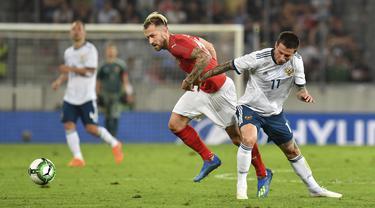 Pemain Austria, Peter Zulj (kiri) berebut bola dengan pemain Rusia, Fedor Smolov pada laga uji coba di Tivoli Stadium, Innsbruck, Austria, (30/5/2018). Austria menang atas Rusia 1-0. (AP/Kerstin Joensson)
