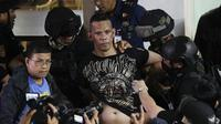 Polisi menahan penyandera Alchie Paray saat ia berbicara kepada media tak lama setelah melepaskan semua sandera di V-Mall di Manila, Filipina pada hari Senin, 2 Maret 2020. (AP Photo/Aaron Favila)