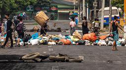 """Seorang pengunjuk rasa membuang sampah di jalan saat demonstrasi menentang kudeta militer di kota Thaketa Yangon, Myanmar, Selasa (30/3/2021). """"Serangan sampah"""" menjadi taktik baru untuk melawan junta militer saat jumlah korban tewas dalam demo anti-kudeta mencapai lebih dari 500. (HO/FACEBOOK/AFP)"""