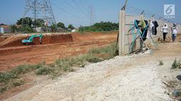 Warga beraktivitas di sekitar pembangunan proyek jalan tol Depok-Antasari di Limo, Depok, Rabu (19/6/2019). Adanya proyek itu diduga menjadi penyebab dua RT mengalami kekeringan sejak dua bulan terakhir, meskipun kejadian serupa belum pernah terjadi sebelumnya. (Liputan6.com/Immanuel Antonius)