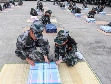 Tentara (kiri) mengajari mahasiswa baru melipat selimut selama sesi pelatihan militer di sebuah kampus di Yangzhou, Jiangsu, China, Jumat (6/9/2019). China memilih pelatihan militer atau dikenal dengan istilah 'Junxun' sebagai program orientasi mahasiswa baru. (STR/AFP)