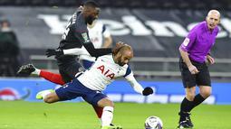 Pemain Tottenham Hotspur Lucas Moura (tengah) berebut bola dengan pemain Brentford Pelenda Joshua Dasilva pada pertandingan semifinal Piala Liga Inggris di Tottenham Hotspur Stadium, London, Inggris, Selasa (5/1/2021). Tottenham Hotspur menang 2-0. (Glyn Kirk/Pool via AP)