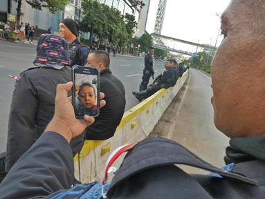 Seorang anggota Brimob melakukan panggilan video dengan anaknya disela penjagaan di kawasan MH Thamrin, Jakarta, Jumat (24/5/2019). Usai kerusuhan 22 Mei 2019, penjagaan di kawasan jalan MH Thamrin sampai Jumat, 24 Mei 2019 masih terus dilakukan oleh aparat kepolisian. (Liputan6.com/Herman Zakharia)