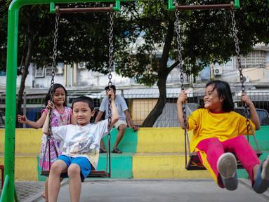 Anak-anak bermain ayunan di Ruang Publik Terbuka Ramah Anak (RPTRA) Rusun Petamburan, Jakarta, Selasa (9/10). Pemprov DKI Jakarta memangkas anggaran pembangunan RPTRA. (Liputan6.com/Faizal Fanani)