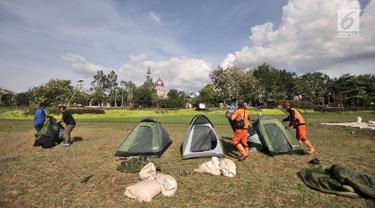 Petugas Penanganan Prasarana dan Sarana Umum (PPSU) mendirikan tenda saat persiapan untuk doa bersama pada malam Tahun Baru di Cipinang Melayu, Jakarta, Minggu (30/12). (Merdeka.com/ Iqbal S. Nugroho)