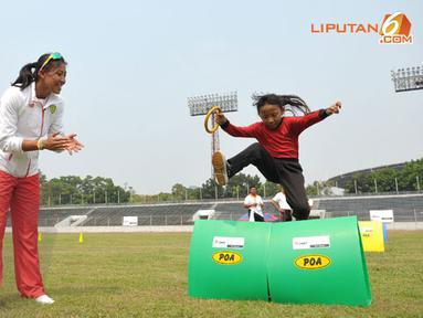 Pelari nasional Dedeh Erawaty mendampingi anak-anak yang mengikuti program pelatihan atletik di Stadion Madya Senayan Jakarta (Liputan6.com/Helmi Fithriansyah)