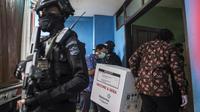 Pekerja membawa masuk vaksin COVID-19 produksi Sinovac setelah diturunkan dari truk pengawalan polisi di Surabaya pada Senin (4/1/2021).  Pemerintah mulai mendistribusikan 3 juta dosis vaksin Covid-19 asal perusahaan China, Sinovac, ke 34 provinsi Indonesia. (Photo by Juni Kriswanto / AFP)