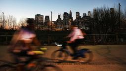 Warga bermain sepeda setelah matahari terbenam saat menikmati taman Brooklyn di New York City (21/2). Cuaca New York akan berubah kembali ke musim dingin dengan suhu yang diperkirakan 30 derajat. (AFP Photo/Spencer Platt)