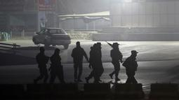 Pasukan keamanan berjalan menuju Hotel Intercontinental setelah serangan mematikan di Kabul, Afghanistan, Sabtu (20/1). Kelompok bersenjata membunuh setidaknya lima orang dan melukai delapan lainnya. (AP Photo/Massoud Hossaini)