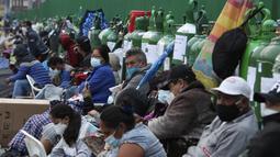 Orang-orang duduk di dekat tabung oksigen kosong mereka saat menunggu toko isi ulang dibuka di lingkungan San Juan de Lurigancho di Lima, Peru, Senin (22/2/2021). Menurut pemerintah, permintaan oksigen medis tumbuh 200 persen di Peru di tengah gelombang kedua Covid-19. (AP Photo/Martin Mejia)