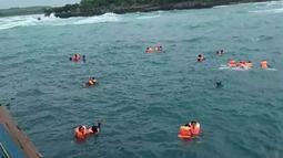Penumpang mengapung di laut saat KM Lestari Maju tenggelam di lepas pantai Pulau Selayar, Provinsi Sulawesi Selatan, Selasa (3/7). Sebagian penumpang KM Lestari Maju yang tenggelam berhasil diselamatkan. (BNPB/AFP)