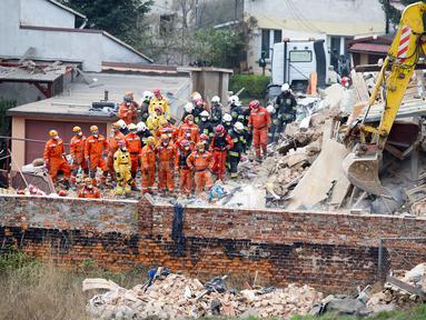 Petugas penyelamat mencari korban di reruntuhan sebuah apartemen tua yang ambruk di Swiebodzce, Polandia, Sabtu (8/4). Akibat insiden itu, 5 orang dikabarkan tewas, sementara 4 orang lainnya luka-luka, dan 1 orang hilang. (Natalia DOBRYSZYCKA/AFP)