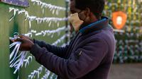 Leonard Makuya, seorang pengurus, mengikat pita ke pagar gereja St James Presbyterian di Bedford Gardens, Johannesburg, Rabu (29/7/2020). Pita tersebut mewakili warga Afrika Selatan yang meninggal akibat virus corona COVID-19. (AP Photo/Themba Hadebe)