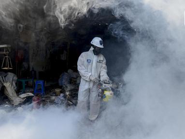 Petugas melakukan fogging nyamuk demam berdarah dengue (DBD) di kampung pemulung Pancoran, Jakarta, Rabu (22/2/2020). Pemerintah mengimbau warga mengantisipasi penyebaran DBD saat musim pancaroba pada April hingga Mei lantaran saat ini terjadi pandemi virus corona COVID-19. (merdeka.com/Imam Buhori)