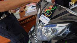 Petugas menempelkan stiker tujuan kota pada motor milik peserta program mudik gratis dari Pemprov DKI Jakarta sebelum dinaikkan ke atas truk di Terminal Pulogadung, Rabu (29/5/2019). Tahap pertama Mudik Gratis Pemprov DKI dimulai dengan pengiriman 712 unit sepeda motor. (Liputan6.com/Faizal Fanani)