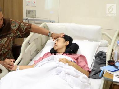 Presiden ke-6 RI Susilo Bambang Yudhoyono atau SBY (kiri) memegang tangan dan mengusap kening sang istri Ani Yudhoyono yang tengah menjalani pengobatan di National University Hospital, Singapura. Ani Yudhoyono dikabarkan meninggal dunia. (Liputan6.com/HO)