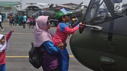 Seorang siswa memegang helikopter pmilik TNI AD ada pameran alat utama sistem persenjataan (Alutsista) di Lanumad  Ahmad Yani Semarang, Jumat (5/10). Pameran alutsista tersebut dalam rangka memeriahkan HUT Ke-73 TNI. (Liputan6.com/Gholib)
