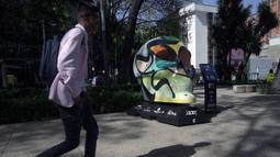 """Seorang pria melewati tengkorak yang dihias selama pameran edisi keempat """"Mexicraneos"""" (Mexisculls) di Reforma Avenue, Mexico City pada 23 Oktober 2020. Pameran tersebut karya seniman dari berbagai bagian negara Meksiko, dan juga dari Amerika Serikat serta Venezuela. (ALFREDO ESTRELLA/AFP)"""