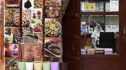Seorang pemilik toko menunggu pelanggan di Deira Souk di kota Emirat Dubai (30/9/2020). Barang yang dijual di Deira Souk juga paling diminati turis seperti rempah dan emas. (AFP/Karim Sahib)