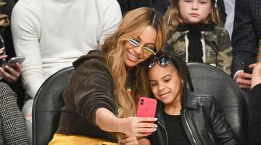 Penyanyi Beyonce dan putrinya Blue Ivy Carter berselfie saat menonton pertandingan NBA All-Star Game 2018 di Staples Center di Los Angeles, California, AS (18/2). (Allen Berezovsky/Getty Images/AFP)
