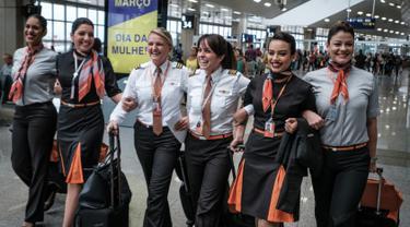 Awak maskapai penerbangan GOL Airlines saat berada di Bandara Internasional Tom Jobim, Rio de Janeiro, Brasil (8/3). Memperingati Hari Perempuan Internasional, GOL Airlines menghadirkan seluruh awak adalah wanita. (AFP PHOTO / Yasuyoshi Chiba)