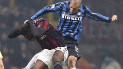 Penyerang AC Milan, Mario Balotelli (kiri) berebut bola udara dengan bek Inter Milan, Joao Miranda pada Liga Italia di Stadion San Siro, Milan (31/01/2016). AC Milan menang telak atas Inter Milan dengan skor 3-0. (REUTERS/Alessandro Garofalo)