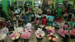Sejumlah pekerja saat merangkai bunga di Pasar Bunga Rawa Belong, Jakarta, Selasa (14/2). Harga bunga impor dari Holland yang biasa dijual 150-200 ribu seikat dijual hingga 300 ribu seikat. (Liputan6.com/Gempur M Surya)