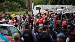 Polisi anti huru hara berjaga di pos pemeriksaan tempat kerabat dari para narapidana berkumpul menyusul kerusuhan yang terjadi di dalam penjara kota Amazon, Brasil, Senin (2/1). Setidaknya 60 orang tewas dalam kerusuhan di penjara (REUTERS/Michael Dantas)