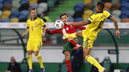Pemain Portugal Bernardo Silva (tengah) berebut bola dengan pemain Swedia Robin Quaison pada pertandingan UEFA Nations League di Stadion Jose Alvalade, Lisbon, Portugal, Rabu (14/10/2020). Portugal menang 3-0. (AP Photo/Armando Franca)