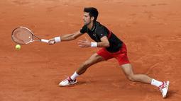 Petenis Serbia, Novak Djokovic melakukan servis ke arah petenis Italia Marco Cecchinato pada perempatfinal Prancis Terbuka 2018 di stadion Roland Garros, Selasa (5/6). Djokovic tumbang 3-6, 6-7, 6-1, dan 6-7. (AP/Alessandra Tarantino)