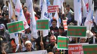 Aksi massa buruh yang tergabung dalam Konfederasi Serikat Pekerja Indonesia (KSPI) di Balai Kota DKI Jakarta, Rabu (1/6). Mereka menuntut kenaikan upah minimum DKI sebesar Rp 650 ribu. (Liputan6.com/Gempur M Surya)