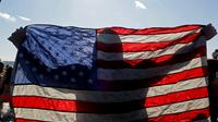 Perenang Polar Bear Club membawa bendera Amerika Serikat bersiap terjun ke air dingin pantai Samudera Atlantik di Coney Island, New York (1/1). Mereka berenang di pantai Samudera Atlantik dengan suhu 17 derajat Fahrenheit. (Yana Paskova/Getty Images/AFP)