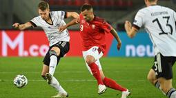 Bek Jerman, Matthias Ginter, berebut bola dengan penyerang Swiss, Haris Seferovic, pada laga lanjutan UEFA Nations League 2020/2021 di RheinEnergie Stadion, Rabu (14/10/2020). Jerman bermain imbang 3-3 atas Swiss. (AFP/Ina Fassbender)