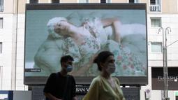 Pejalan kaki melewati layar yang menunjukkan model Vivetta selama Milan Digital Fashion Week, di Milan, Italia pada 14 Juli 2020. Empat puluh rumah mode menampilkan koleksi pakaian untuk musim semi/musim panas 2020 dalam format digital di tengah pandemi Covid-19. (AP Photo/Luca Bruno)
