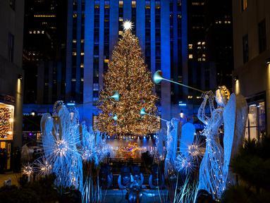 Lebih dari 50.000 lampu menghiasi Pohon Natal Rockefeller Center setinggi 75 kaki pada upacara tahunan pencahayaan di New York, Rabu (2/11/2020). Upacara yang digelar pada masa pandemi COVID-19 ini mewajibkan pengunjung untuk memakai masker, pembatasan waktu, dan jaga jarak. (AP Photo/Craig Ruttle)