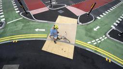 Seorang pesepeda menunggu pergantian lampu lalu lintas di jalur sepeda persimpangan CYCLOPS (Cycle Optimized Protected Signals) di wilayah selatan Manchester, Inggris (9/7/2020). Persimpangan CYCLOPS ini dibuat untuk mengurangi kemungkinan terjadinya tabrakan atau konflik. (Xinhua/Jon Super)