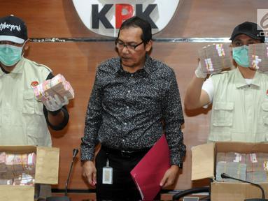 Wakil Ketua KPK Saut Situmorang bersama petugas menunjukkan barang bukti uang 2,5 Miliar hasil OTT di dua wilayah Kota Blitar dan Kabupaten Tulungagung, Jakarta, Jumat (9/6). (Merdeka.com/Dwi Narwoko)