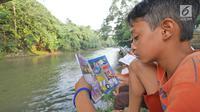 Anak-anak membaca buku di Saung Pustaka Air di Depok, Jawa Barat, (30/5). Perpustakaan ini menjadi sarana edukasi untuk menjaga dan mengenalkan area konservasi keanekaragaman hayati. (Liputan6.com/Herman Zakharia)