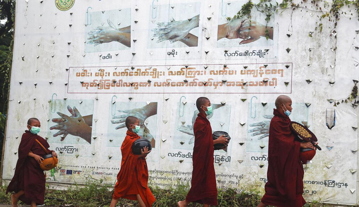 Biksu Buddha mengenakan masker berjalan melewati papan peringatan COVID-19 saat mereka mengumpulkan sedekah pagi di Yangon, Myanmar, Kamis (15/7/2021). Hampir 90 persen wilayah di Myanmar telah terkena dampak gelombang ketiga Covid-19. (AP Photo/Thein Zaw)