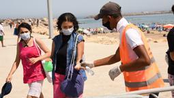 Petugas kesehatan membantu seorang wanita membersihkan tangannya di sebuah pantai di Rabat, Maroko, 27 Agustus 2020. Maroko pada 27 Agustus 2020 melaporkan 1.221 kasus baru COVID-19, menambah jumlah kasus infeksi di negara itu sejak 2 Maret menjadi 57.085. (Xinhua/Chadi)
