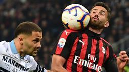 Bek AC Milan, Mateo Musacchio mengontrol bola dari kawalan bek Lazio, Riza Durmisi selama pertandingan lanjutan Liga Serie A Italia di stadion San Siro (13/4). Milan menang tipis atas Lazio 1-0. (AFP Photo/Miguel Medina)