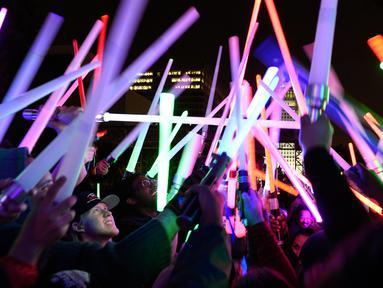 Penggemar film Star Wars berkumpul sambil membawa lightsaber (pedang sinar) saat mengikuti Glow Battle Tour di Grand Park, Los Angeles (15/12). Mereka berkumpul dengan membawa pedang sinar yang beraneka warna. (Photo by Chris Pizzello/Invision/AP)