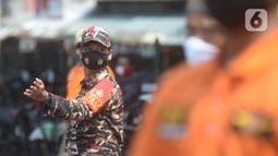 Anggota Organisasi Kemasyarakatan atau Ormas membantu Satpol PP dalam Operasi Yustisi Protokol Kesehatan Covid-19 di Terminal Kampung Melayu, Jakarta, Kamis (24/9/2020). Operasi Yustisi untuk menegakkan disiplin dalam penerapan protokol kesehatan itu melibatkan Ormas. (merdeka.com/Imam Buhori)