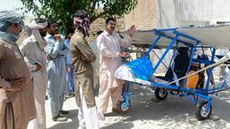 Muhammad Fayyaz berbincang dengan warga yang melihat pesawat buatannya di Desa Tabur, Provinsi Punjab, Pakistan, 8 April 2019. Karya lelaki berusia 32 tahun tersebut berhasil menarik perhatian Angkatan Udara Pakistan. (ARIF ALI/AFP)