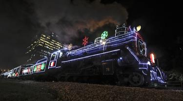 Kereta wisata yang dihiasi lampu Natal terlihat di Bogota (20/12/2019). Meyambut Hari Natal, kereta wisata di Kolombia membuat cara unik dengan memasangkan lampu warna-warni agar menjadi daya tarik penumpang. (AFP Photo/Juan Barreto)
