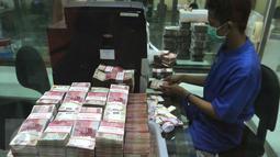 Petugas Bank sedang menghitung uang, Jakarta, Senin (2/11/2015). Lembaga Penjamin Simpanan (LPS) mencatat jumlah rekening simpanan dengan nilai di atas Rp2 miliar pada bulan September mengalami peningkatan . (Liputan6.com/Angga Yuniar)